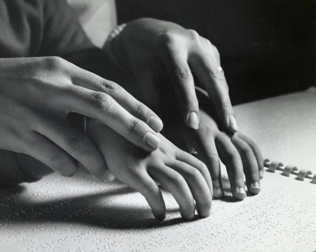 Close up black and white image of 4 hands. A grown-up guides the hands of a child while they read a book published in Braille.