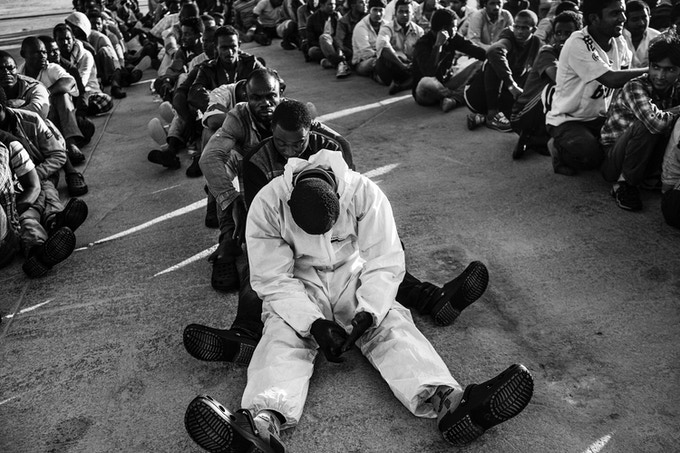 """Sub-Saharan refugees sit on the dock at the port of Augusta, Sicily waiting to be transferred to the first reception area. This is one of four images available as a print with the limited edition of """"The Dream""""."""