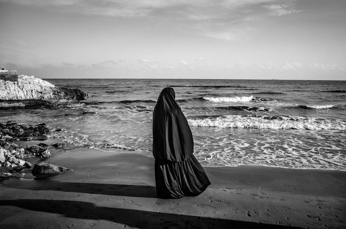 """Syrian woman refugee observes the sea at the beach in Kiz Kalesi, while waiting to be allowed to board an illegal ship for Europe. This is one of four images available as a print in the limited edition of """"The Dream""""."""