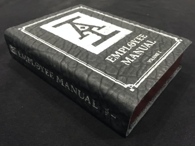 The AI Employee Manual is crafted in rich mahogany with a walnut trim, steel reflecting pool, onyx leather, and exclusive Penny Arcade cover and spine art