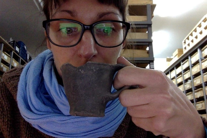 Maja, having a Bronze Age cup of coffee (Storehouse of the Korçe University, Albania, Early Bronze Age cup from Sovjan, 2200 BCE)
