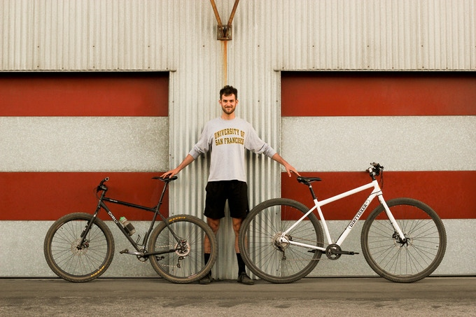 "6'10"" Alex between a regular XXL bike and our production DirtySixer."