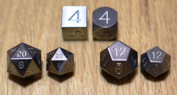 Large and small version of the tungsten dice. You'll receive the large versions of the D20 and D12 and you can choose rounded or square cornered for the D6