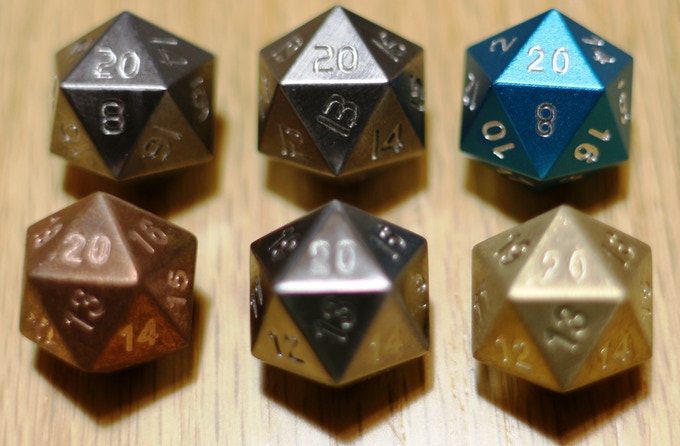 Tungsten Standard next to a Tungstne Spindown die shown next to standard Aluminum Teal D20 for size and numbering comparison