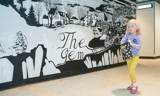Madison Lambert, 3, leaves an afternoon screening at The Gem movie theater in Bethel on Sunday. The mural in the background was created by artist Mattie Rose Templeton using imagery of historic Bethel. Photo by Andree Kehn / Lewiston Sun Journal