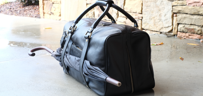 Need an extra hand? The Duffle Suitcase is happy to help with your umbrella or newspaper