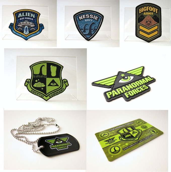 """All the items in the """"Cryptid Command"""" main kit —Alien Air Force, Nessie Navy and Bigfoot Army patches, along with the Cryptid Command 4up shield patch, a Paranormal Forces PVC emblem, a printed dog tag and a plastic ID card."""