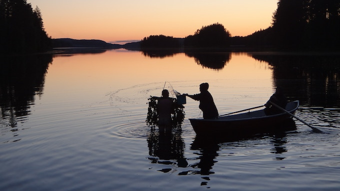 Riitta delivers a bucket of hot water to warm up Jaska on a chilly Midsummer's Eve in North Karelia.