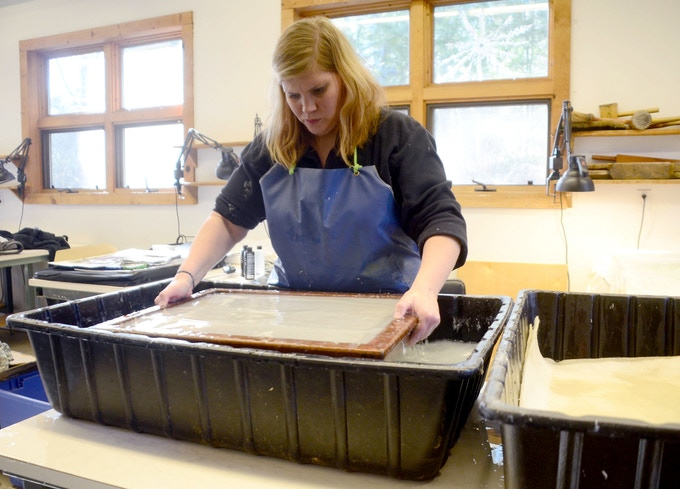 Trish Brownlee pulling a sheet of handmade paper, pulped from military uniforms