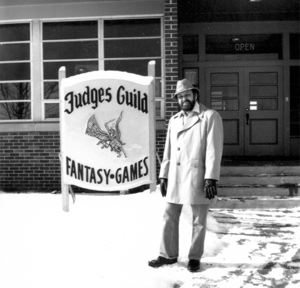 Vintage photo of Judges Guild co-founder and creative visionary Bob Bledsaw in front of the Judges Guild offices in Decatur, IL