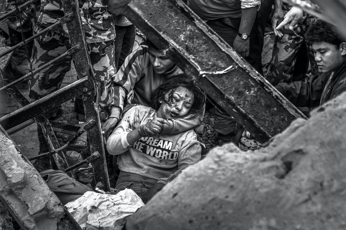 Emergency rescue workers and bystanders find a survivor in the debris. Minutes after the earthquake hit Nepal, teams of volunteers and response units started working trying to find survivors under the debris in the historic area of Kathmandu.