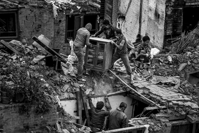 Residents salvage a wardrobe through the roof of their home on April 29, 2015 in Bhaktapur