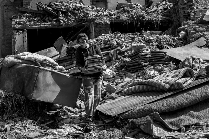 A young girl salvages books from her collapsed house in Harisiddhi a week after the earthquake