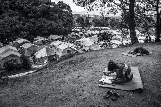 A displaced girl studies on a hill in front of the Bode displacement camp on in Bhaktapur. More than 1000 people who lost their homes lived in the camp in August of 2015.