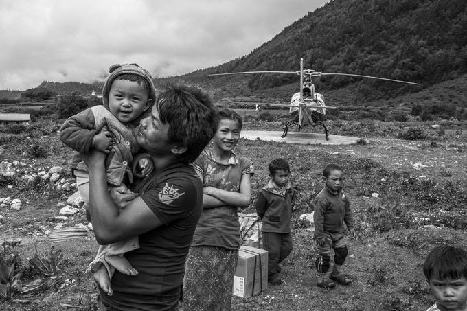 Thirty-one year old Sukhman Tamang holds one of his youngest relatives after landing at his village in the Himalayas with his wife and daughters two months after being evacuated