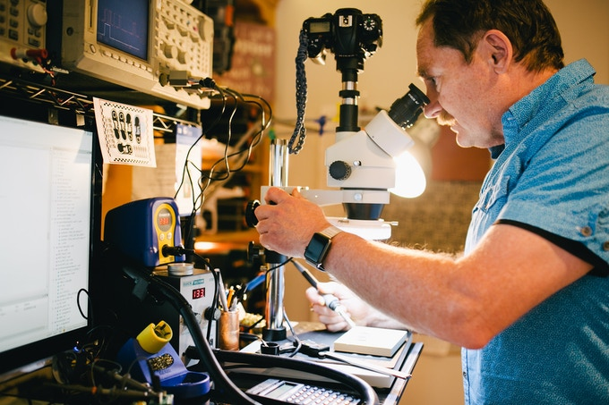 Co-Founder Mike Coryell uses a microscope to assemble our tiny prototype.