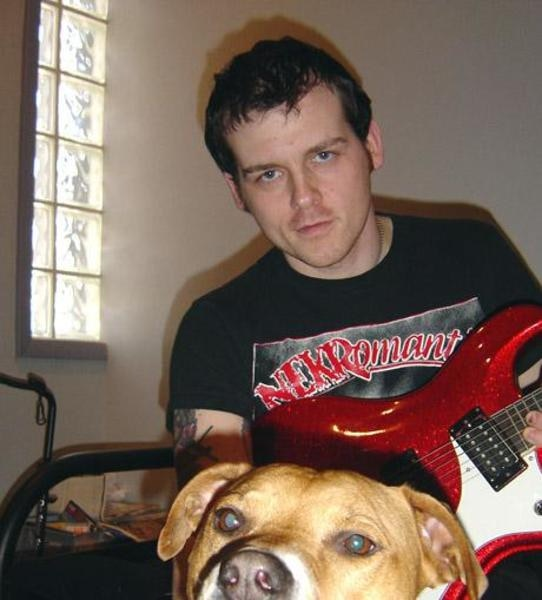 """Derek Grant of Alkaline Trio recording additional guitar tracks for a trio of songs for the """"Remains"""" album accompanied by studio manager pooch Daysi."""