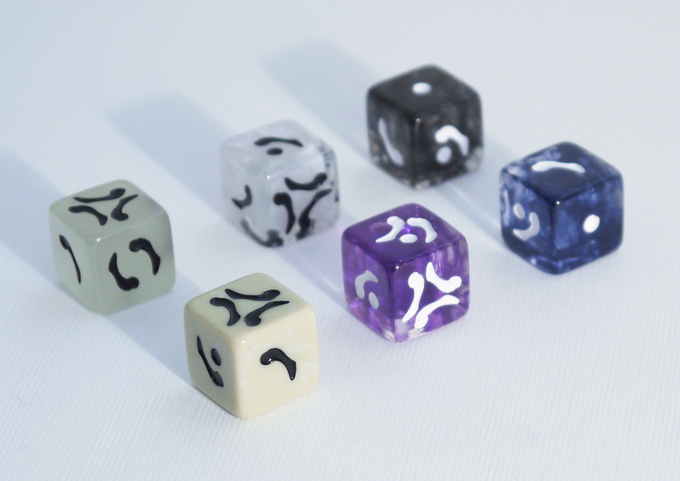 Photo of the production ready D6 samples of the D6 dice. Front row: Bone Ivory, Occultist Purple, Nightmare Blue. Back row: Glow in the Dark, Bone Mist, Charred Smoke.