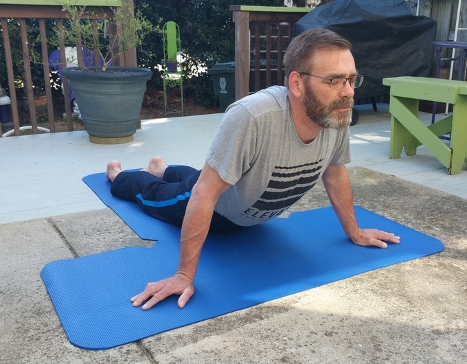 John practices yoga poses outside on his back deck area.