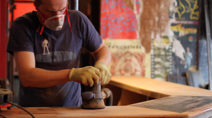 An artisan carpenter skilfully prepares the bar, ready for you to name.
