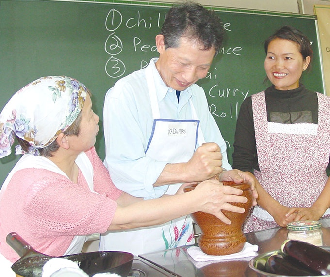 On tour in Japan, helping students with a mortar and pestle