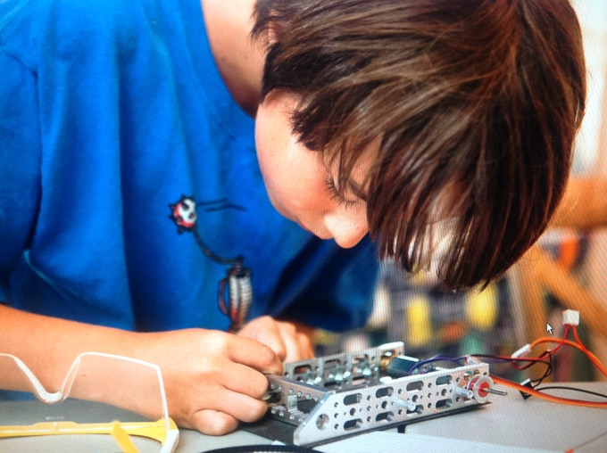 Nine-year-old working on a robot of his own design