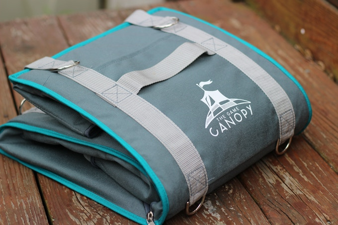 The Game Canopy and Vanguard fold down compactly ~ this makes it easy to carry them in your luggage when traveling to conventions or for storing in-between game nights. Shown here is the Grey base-color with the Peacock Teal trim.