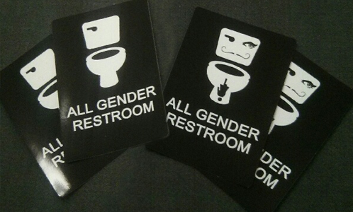 "[a small spread of vinyl ""all gender restroom"" stickers]"