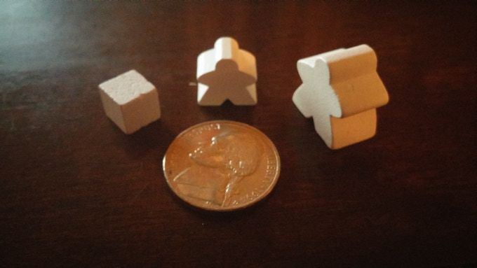 A picture of the cubes from the retail version compared with the mini-meeples and 3-count full size meeples from the deluxe version.