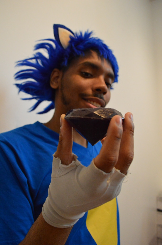 """Cosplayer Khalil Crocker as Sonic the Hedgehog, holding one of our """"Candy Chaos"""" edible emeralds."""