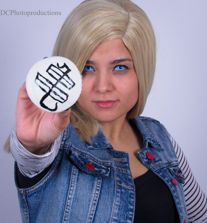 Cosplayer KayshaChaos as Android 18 holding one of our Kreamcicle Krillin Cupcakes.