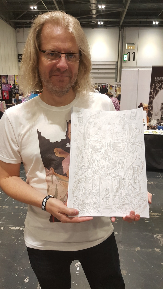 Simon Birks holding one of the original A3 inked pages by Lyndon White