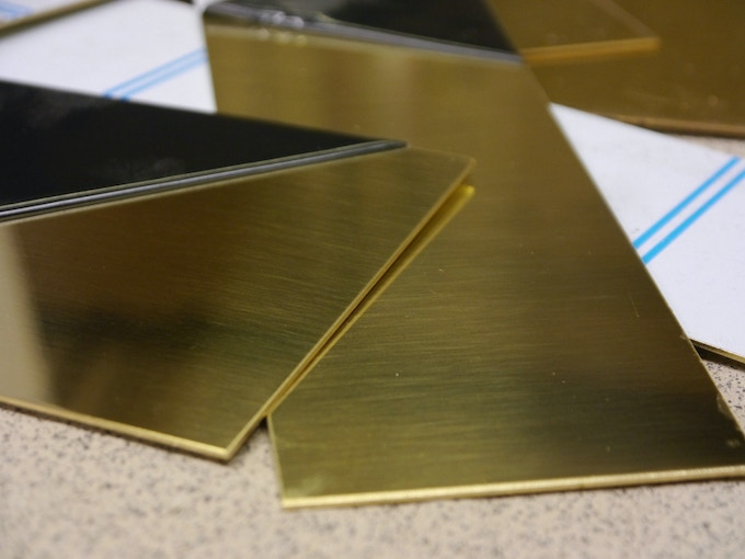 Raw sheets of brass waiting to be laser cut and engraved