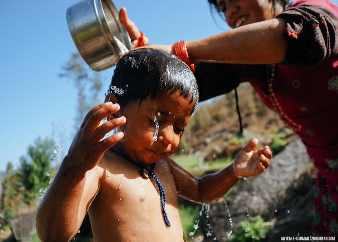 Mother washing a child in Japhe village.