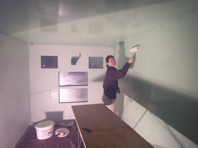 Coating the walls and ceiling with an adhesive designed for glass fibre wall paper.