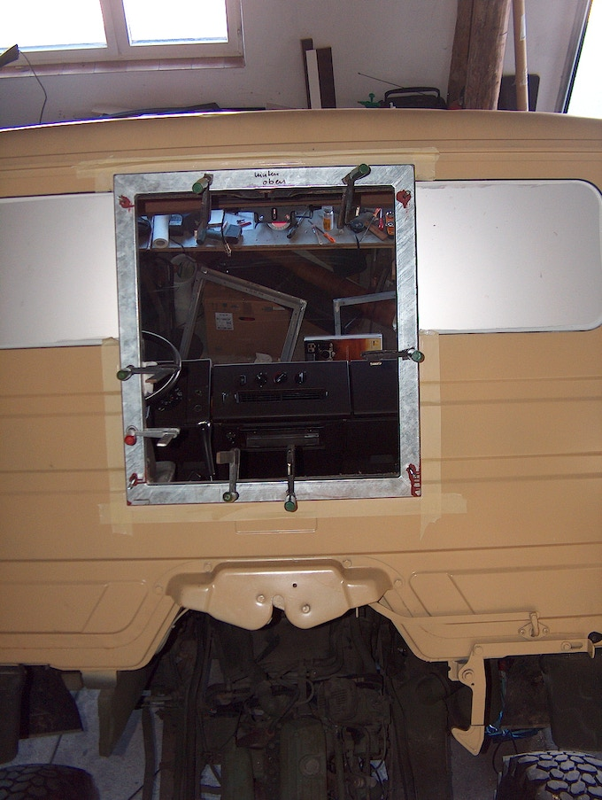 The metal frame is bonded to the cockpit using PU adhesive and positioned with C-clamps.