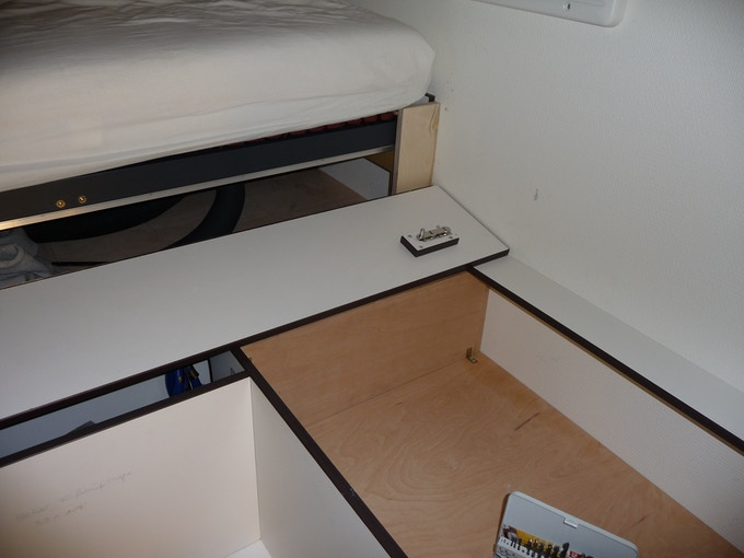 Hatch opened to reveal the shelf in the storage area under the bed.