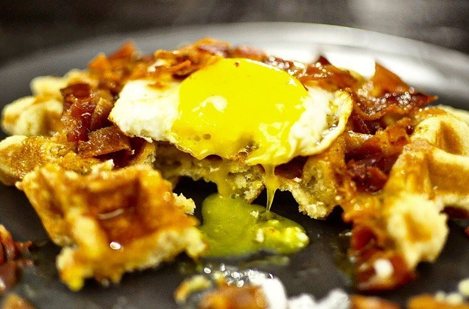 The American - Our Classic Liege Waffle topped with thick cut bacon, a sunnyside up egg, and pure maple syrup.