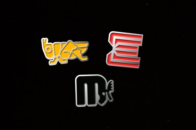 Enamel pin badges featuring three of Lance Wyman's iconic logos