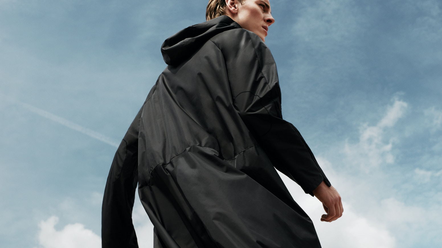 A minimal, unisex raincoat completely adapted to urban commuting, like cycling.