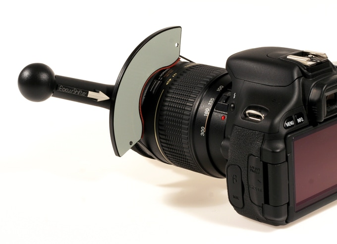 The marker board attaches to a non-rotating part of the lens. The extra space on this zoom lens allows proper attachment.