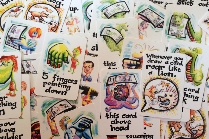 Two hands touching. Cards balanced on your body. A hand on a knee. Can you draw a card? Roar like a lion! Thumbs up!