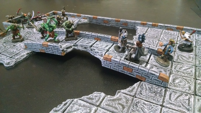 A large chasm spanned by a crumbling stone bridge guarded by orcs.