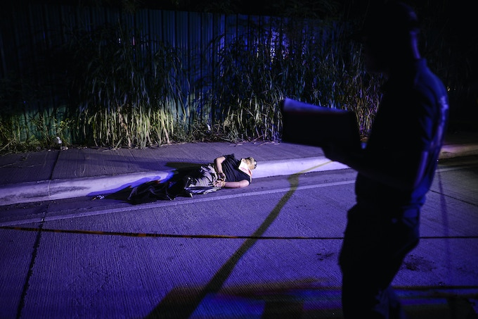 A police investigator inspects the corpse of a suspected drug addict and victim of a vigilante-style execution with his hands tied and head wrapped with tape on a street in Pasay, south of Manila. This is one of images available as a print.
