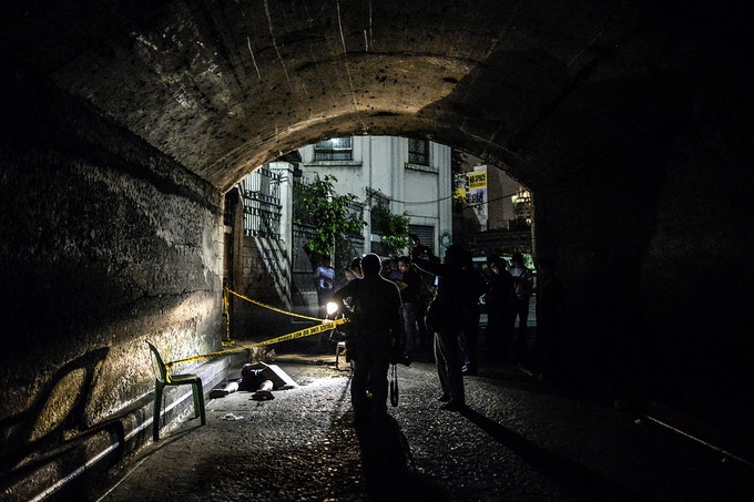 Police and media inspect the corpse of a suspected drug pusher and victim of a vigilante-style execution under a bridge in Manila. This is one of images available as a print.