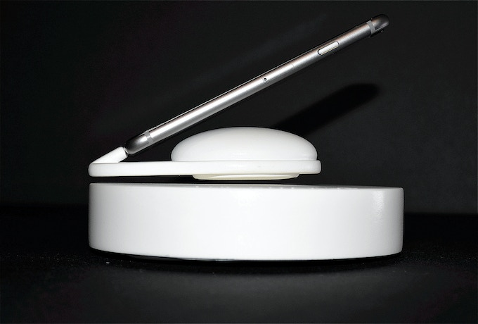 The charging puck only makes contact with the iPhone through the Lightning Connector