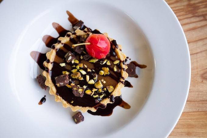 Salted Caramel Tart - chocolate ganache, chocolate fudge, pistachios, poached crabapple