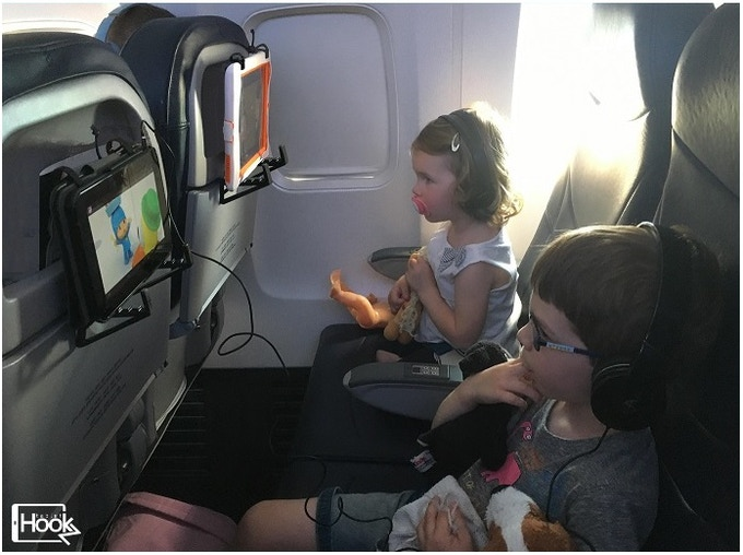 The children happy and relaxed with their tablet mounted in the TabletHookz™ on the airline seats