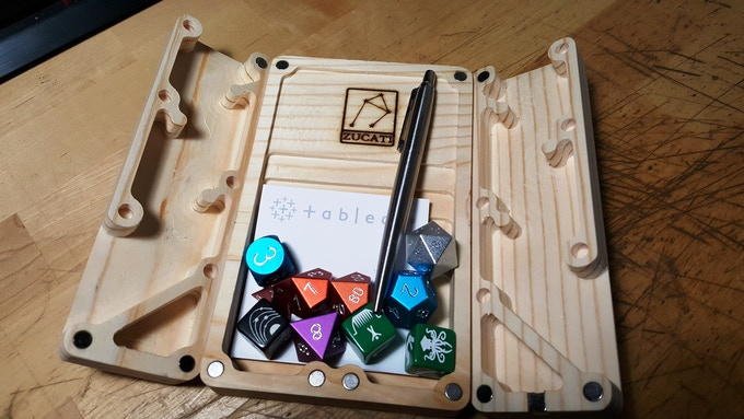 But wait, this isn't your average gaming accessory. Like everything from ZucatiCorp there's more than one use for all parts! Inside you can store a pad of sticky- notes, more than a full set of dice and a pen, or two!