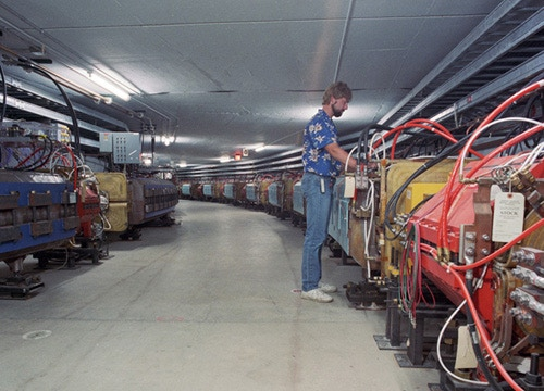 Fermilab accelerator operations specialist inspecting components in the antiproton Accumulator storage ring.  The Debuncher accelerator is behind him on the inside wall of the tunnel.